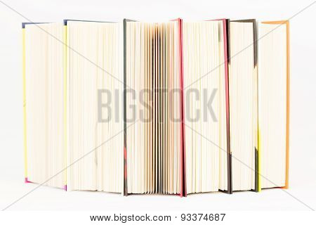 Stack of colorful books are standing on the edge.