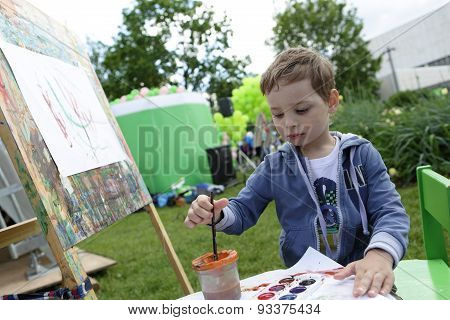 Boy Painting At Easel