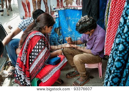 Indian Man Painting Henna Paste On Woman's Hand At The Russell Market In Bangalore