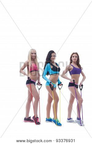 Pretty sportswomen exercising with expanders