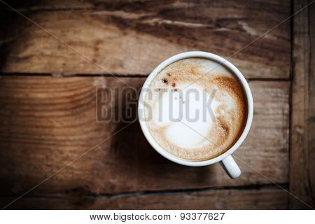 Cup Of Coffee With Heart Pattern In A White Cup On Wooden Background. Latte Art