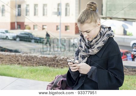 Lifestyle Concepts: Teenager Girl Using Cellphone Outdoors.