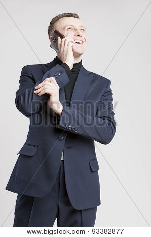 Business Concept: Young Caucasian Businessman In Blue Suit Speaking Using Cellphone. Over White Back