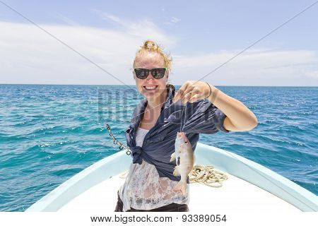 Woman Holding Up A Fish
