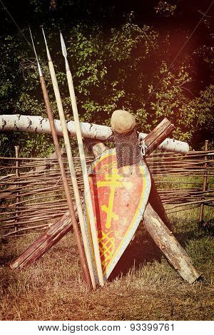 three spears, a shield with an Orthodox cross with a helmet and chain mail about wicker fence