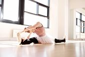 stock photo of leg-split  - Young Flexible Ballerina Splitting her Legs While Reaching her Toes During her Warm up Exercise at the Studio - JPG