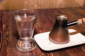 picture of pot roast  - A turkish coffee pot and a cup of water on a wooden surface - JPG