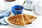 picture of crepes  - Homemade Crepes Folded In Triangles With Black Currant Jam And Cup Of Tea - JPG