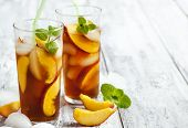 stock photo of iced-tea  - Peach Ice Tea in glass cup on wooden background with copy space - JPG