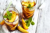 stock photo of iced-tea  - Glasses Of Peach Iced Tea on wooden table - JPG