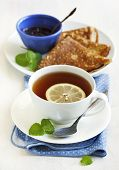 stock photo of crepes  - Cup Of Lemon Tea And Crepes With Jam  - JPG