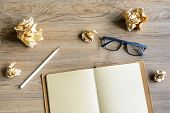 stock photo of stress-ball  - Crumpled paper balls with eye glasses and notebook on wood desk creative writing concept - JPG