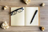 image of stress-ball  - Crumpled paper balls with eye glasses and notebook on wood desk creative writing concept - JPG