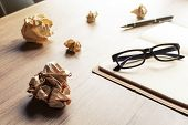 picture of stress-ball  - Crumpled paper balls with eye glasses and notebook on wood desk with soft light - JPG