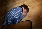 image of child abuse  - Child abuse composition of a frightened young boy lying on the wooden floor in a light of a flashlight circle - JPG