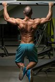 stock photo of pull up  - Young Male Athlete Doing Pull Ups - Chin-Ups In The Gym  ** Note: Shallow depth of field-face... - JPG