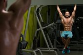 picture of abs  - Young Man Performing Hanging Leg Raises Exercise  - JPG