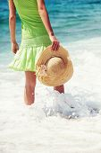 stock photo of beach hat  - Woman holding hat and walking on the beach - JPG