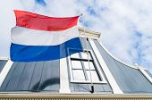stock photo of holland flag  - dutch flag in front of an authentic dutch house facade - JPG