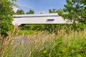 stock photo of covered bridge  - The historic white Moscow Covered Bridge in rural Rush County Indiana spans the Flatrock River - JPG