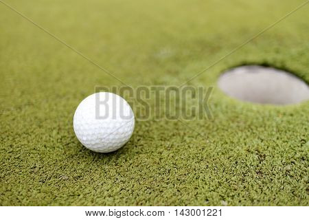 golf ball and hole on a golf course