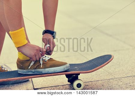 one skateboarder hands tying shoelace at city