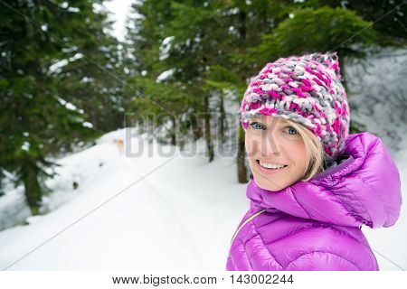Woman hiking in white winter forest woods with akita dog. Recreation fitness and healthy lifestyle outdoors in nature. Motivation and inspirational winter landscape.