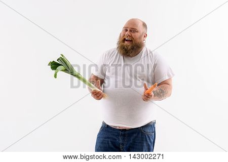 I like healthy food. Happy fat man is holding carrot and leek. He is standing and smiling. Isolated