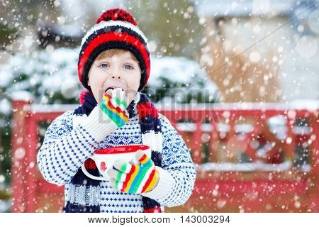 Cute little boy holding big cup with snowflakes and hot cocoa and chocolate drink and marshmallows. Kid boy in winter sweater, hat, long warm scarf and colorfull gloves.