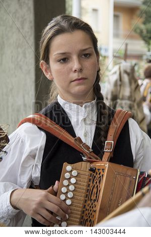 QUARTU S.E., ITALY - September 15, 2013: Wine Festival in honor of the celebration of St. Helena - Sardinia - portrait of a beautiful girl in Sardinian costumes and plays the accordion