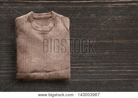 Folded wool pullover on dark wooden background