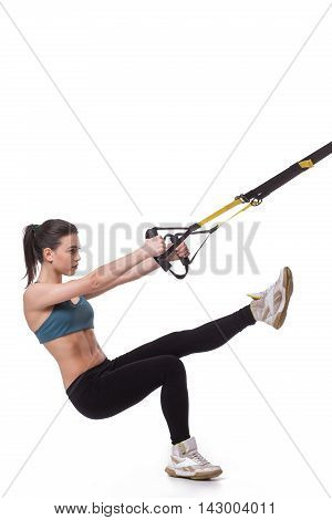 Upper body excercise concept. Picture of young woman using suspension trainer sling for exercising her body. TRX concept. Studio shot.
