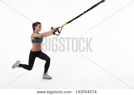 Upper body excercise concept. TRX concept. Studio shot. Image of young beautiful woman training with suspension trainer sling isolated on white background.