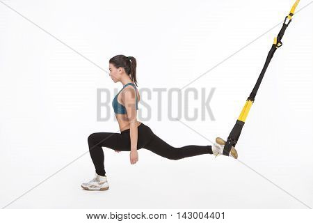 Young attractive woman doing suspension training with fitness straps in studio. Beautiful lady training with suspension trainer sling.