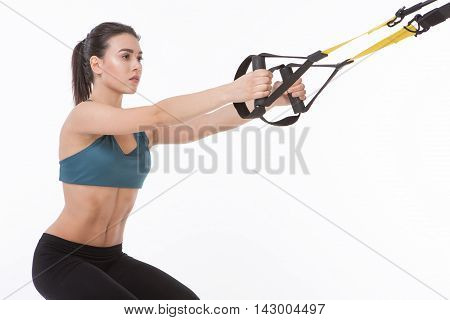 Core body excercise concept. Closeup picture of beautiful lady training with suspension trainer sling or TRX in studio. Studio shot.