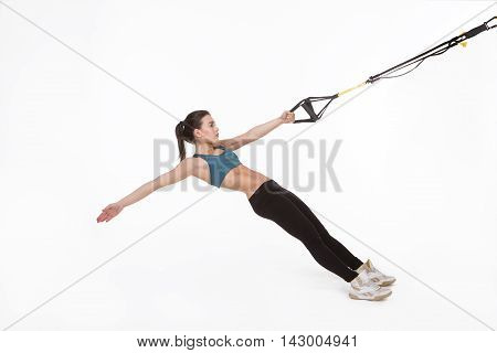 Picture of fitness trainer posing for photographer while training with suspension trainer sling or suspension straps. TRX concept.