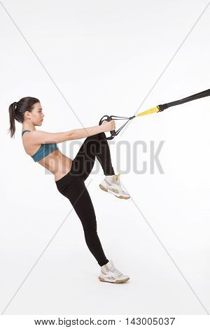 Attractive young woman exercising with modern sports equipment. Picture of fitness lady training with suspension trainer sling or suspension straps in studio.