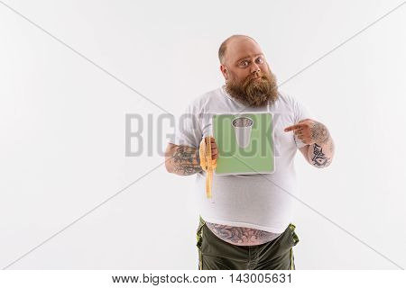 Fat man is holding scale with pointing finger at it. He is looking at camera with proud. Man is standing and carrying measuring tape. Isolated and copy space in left side