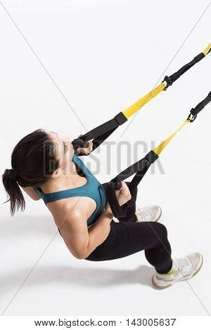 Beautiful woman excercising in studio. Lady using TRX equipment. Top view of pretty young lady training upper body on suspension trainer sling.