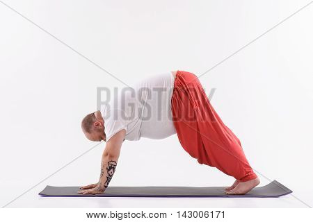 Calm fat man is doing yoga and relaxing. He is posing on mat. Isolated