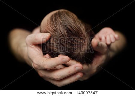 Newborn baby in father's hands on black