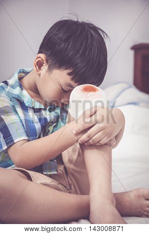 Childhood accidents. Sadness asian boy worry about wound on his knee with bandage. Child injured on bed in bedroom. Human health care and medicine concept. Vintage tone effect.