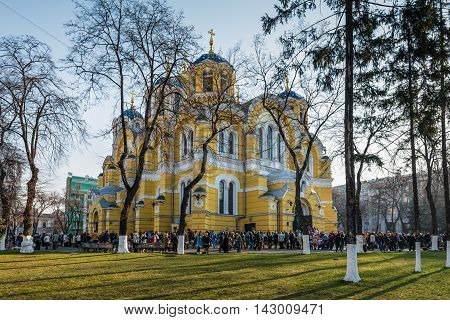 Kyiv Ukraine - April 12 2015: People waiting for blessing his baskets of food during Holy Easter Sunday ceremony outside St Volodymyr's Cathedral in Kyiv Ukraine. It is one of the city's major landmarks and the mother cathedral of the Ukrainian Orthodox C