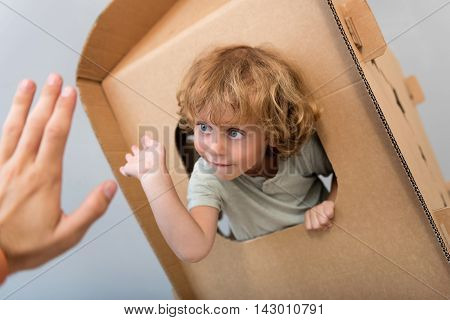Take it. Captivating little boy sitting in the carton rocket and giving five to a hand of a man through the window