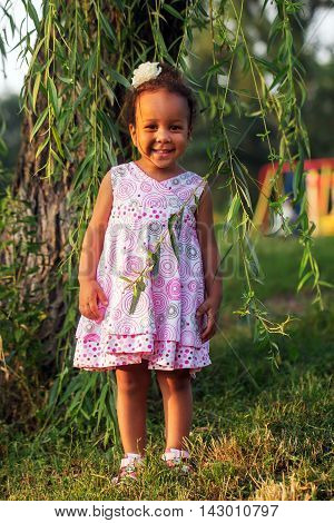 Happy smiling black baby girl outdoors. Baby walking in the park.