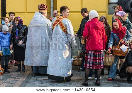 Kyiv Ukraine - April 12 2015: Priest blessing the happy people during Holy Easter Sunday ceremony outside St Volodymyr's Cathedral in Kyiv Ukraine.