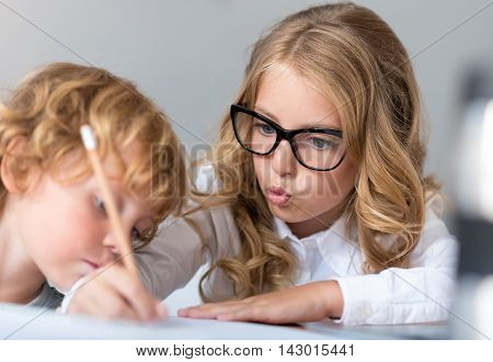 Look attentively. Sophisticated little girl with glasses writing and explaining it to the little boy who looking attentively at the notebook
