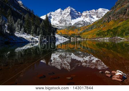 Beautiful Colorado Rocky Mountain Autumn Lake Reflection with snow and colorful aspen leaves in Maroon Bells Wilderness