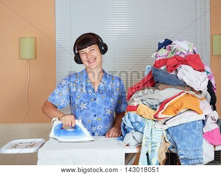 Young Caucasian Woman Ironed Clothes And Listening To Music On Headphones In The Room Near Window.