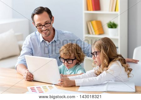 Followers in success. Mature man sitting at the table and looking at the screen of the laptop with adorable little boy and girl